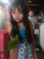 Jenessa with a parrot, Johnny in the background.